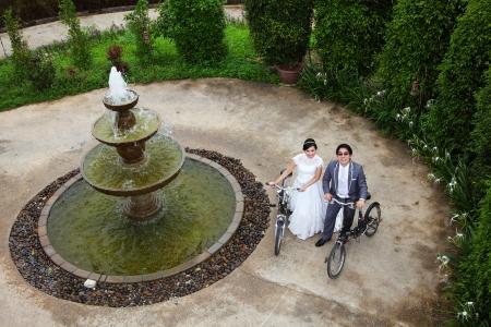Wedding couple with bikes near fountain