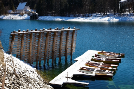 Floating boats covered in snow at Walchensee lake in Bavaria Germany