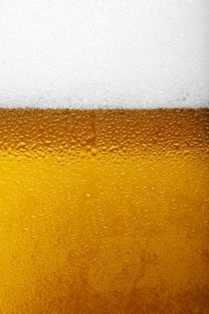 Close-up foto van een bier met schuim en bubbels