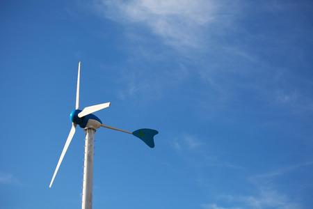 Green renewable energy concept - wind generator turbines on blue sky background