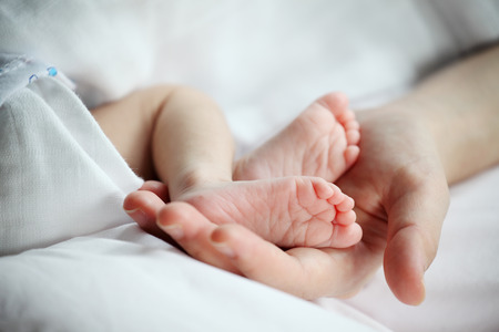 baby's feet: Babys Feet in Mother Hand Closeup Stock Photo