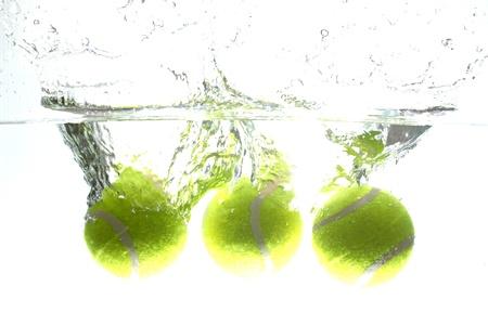 Pelota de tenis se dej? caer en el agua, haciendo que el agua propagaci?n. Foto de archivo