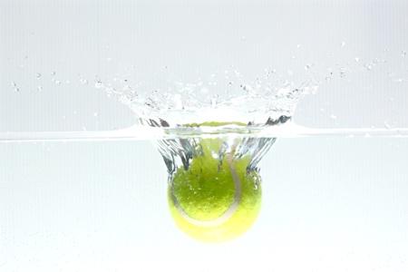 Pelota de tenis se dej?er en el agua, haciendo que el agua propagaci?