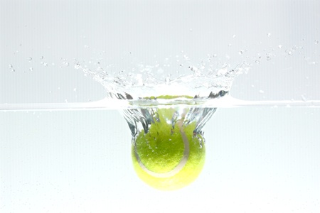 causing: Tennis ball dropped into the water, causing spread water.