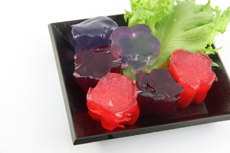 coagulate: Red jelly and purple jelly in dish on the white background.
