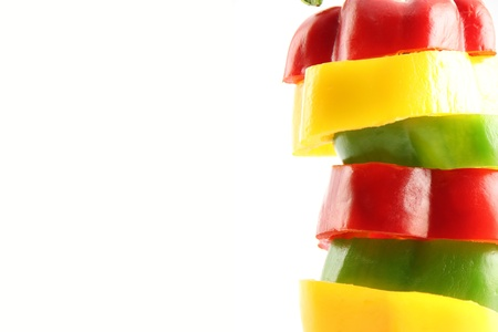 Slice the Three color of bell pepper in Arranged vertically on white background.