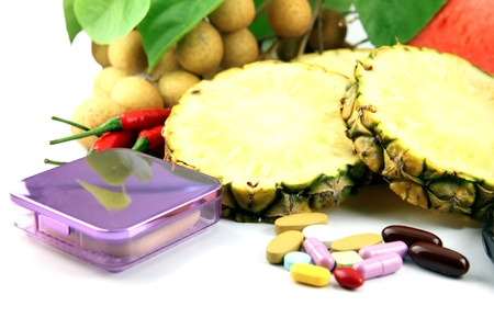 Fruits and medicines placed near the cosmetics on white background. photo