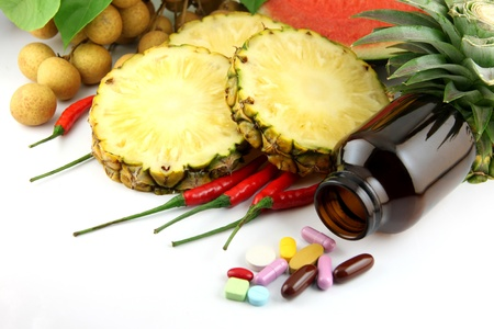 Fruits and medicines placed near the cosmetics and Vegetables on white background. photo