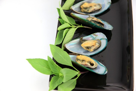 The picture Mussel on black dish and Vegetables placed beside. photo