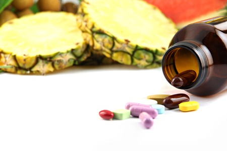 Fruits and medicines placed near the cosmetics on white background  photo