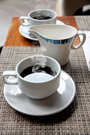 The picture hot Black coffee in a white cup on the table and have smoke coming out. photo