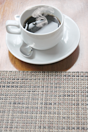 The White Coffee cup with heat on the table. photo