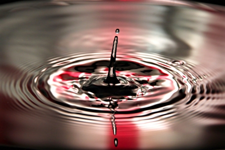 Closeup Pictures Red Background of Water drops a beautiful shape in Basin. Stock Photo - 22174670