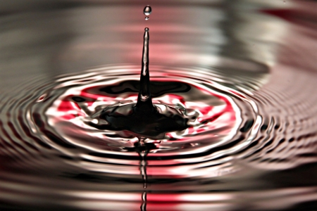Closeup Pictures Red Background of Water drops a beautiful shape in Basin. Stock Photo - 22174689