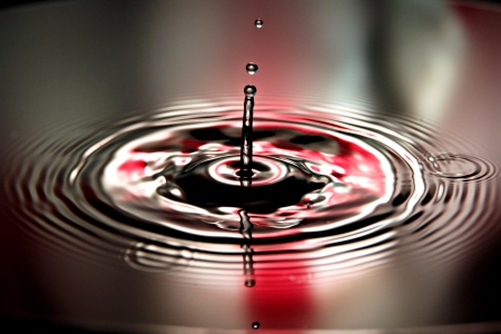 Closeup Pictures Red Background of Water drops a beautiful shape in Basin. Stock Photo - 22437489