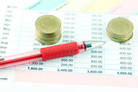proceedings: Closeup Picture Red Pen and money Coins on the Business graph. Stock Photo
