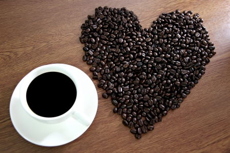 The concept of the lead Coffee beans arranged shaped into a heart near white coffee cup. photo