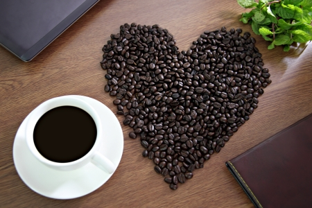 The Picture of Coffee beans arranged in a heart shape, close to Coffee White and green Peppermint. photo