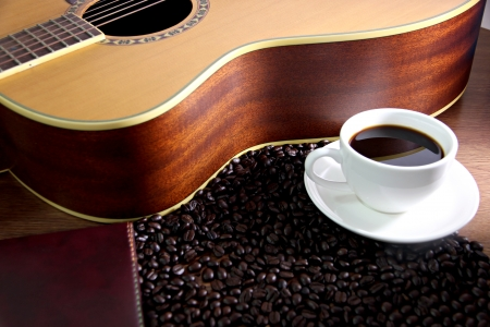 The Concepts that White coffee cup resting on guitar and coffee beans. photo