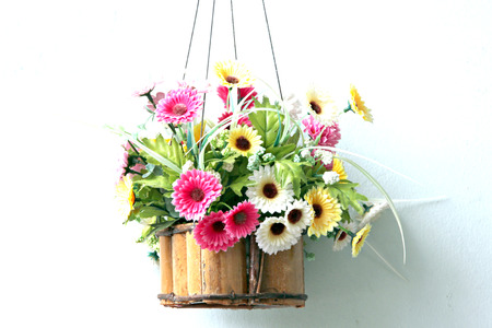 Colorful flowers in a wooden basket and it was hanging out. Stock Photo