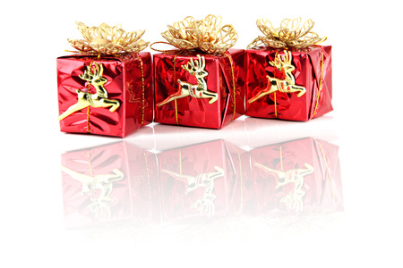Red gift box with golden Reindeer attached. photo