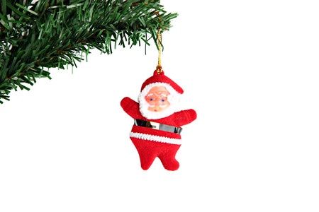 Santa hanging on branch of Christmas tree. photo