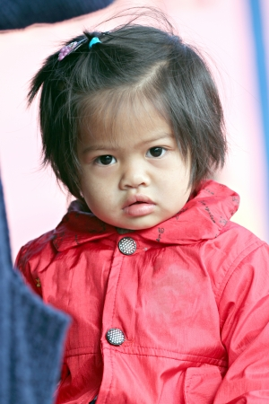 Asian baby child girl in red dressed,She stares at the camera  photo