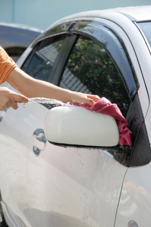 White car washing with fabric and Water hose in house. photo