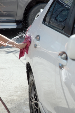 water hose: White car washing with Water hose in house.