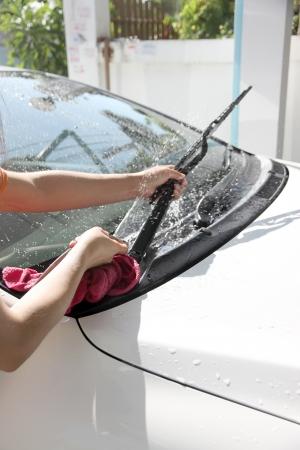 ruitenwisser: Witte auto wassen Ruitenwisser met slang Water in huis.