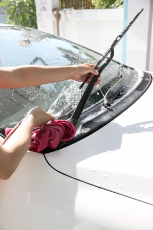 White car washing Windshield wiper with Water hose in house.