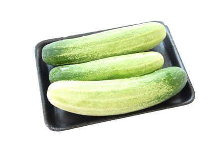 cucumber in black tray container isolated on white background. photo