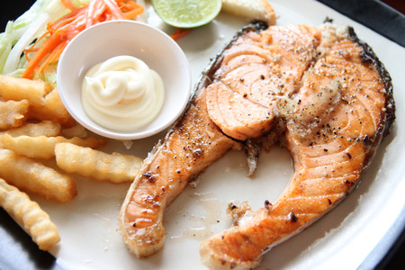 grilled salmon steak with french fries and toast on the table in restaurant. photo