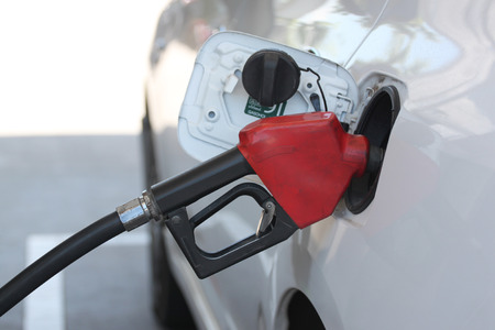 Red fuel nozzle in pouring to car on gas station. photo