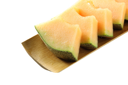 Cantaloupe melon isolated in bamboo dish on white background. photo