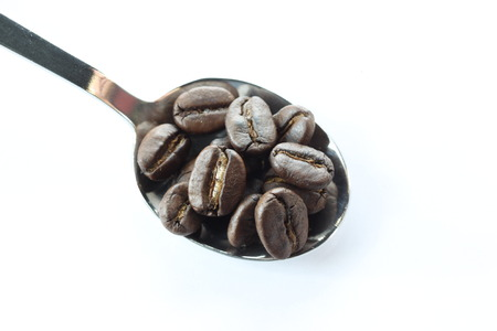 Coffee beans in a stainless steel spoon on white background. photo