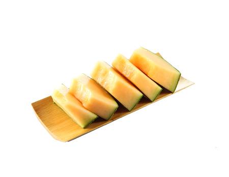 Cantaloupe melon isolated in bamboo dish on white . photo