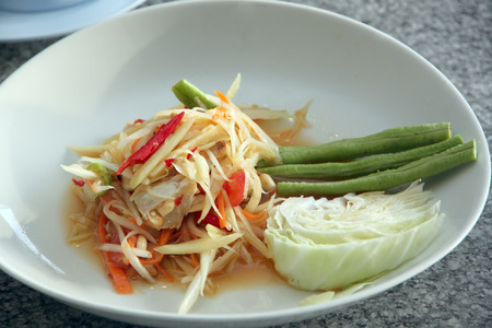 green papaya salad in white dish on the foods table. photo