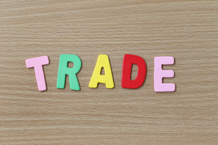 wood trade: The Trade of colorful text on a brown wood . Stock Photo