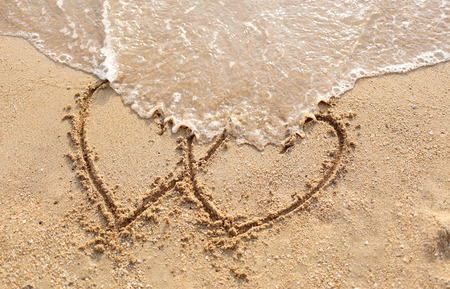 Beaches waves and heart shape drawn in the sand. photo
