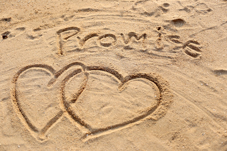 The heart shape and promise text drawn in the sand.