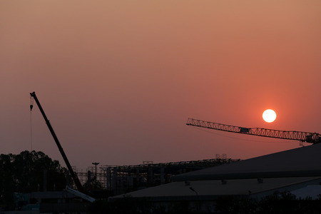 closing time: Sunset and plant currently under construction in the evening.