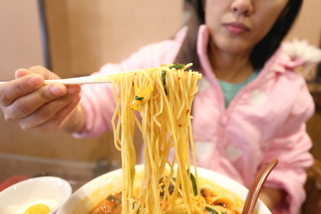 Chopsticks are clamp Ramen noodles in Japanese Restaurant. photo