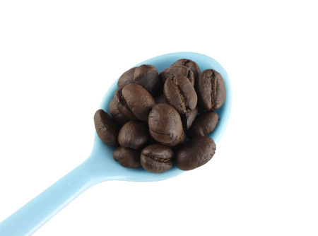 objects with clipping paths: Coffee beans in blue plastic spoon isolated on white background with clipping paths.