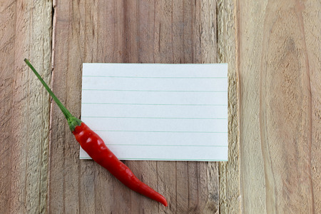 red peppers: Note paper and Red peppers on wood background.