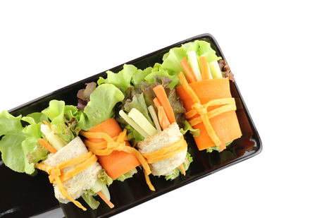 black dish: roll salad in the black dish on white background  Stock Photo