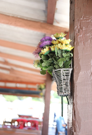 bogus: Colorful fake flowers stuck on a wooden pole. Stock Photo