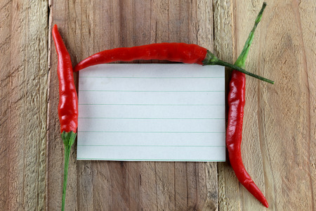 note paper: Note paper and Red peppers on wood background.