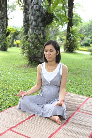 mental activity: Thai pregnant mom was meditation in the garden for good mental health.