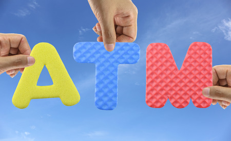 withdraw: Hand arrange alphabet ATM of acronym Automatic Teller Machine for withdraw money. Stock Photo